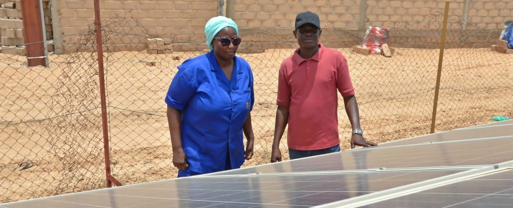 A woman and a man are inspecting solar panels in front of a house