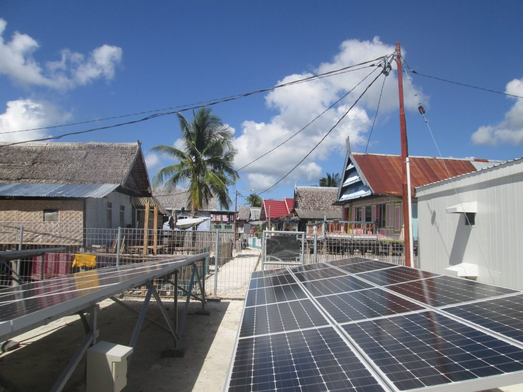A photovoltaic minigrid is seen in front of the houses of an Indonesian village.