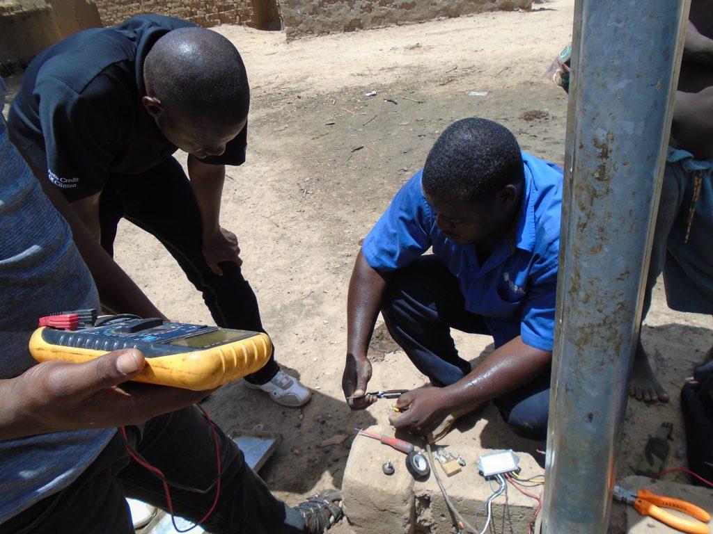 Three Malian technicians are conducting a streetlight maintenance.