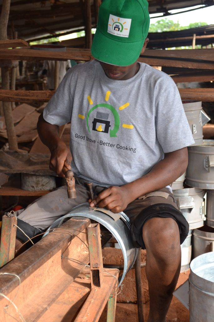 A Ugandan man is working on an improved cookstove made of stainless steel.