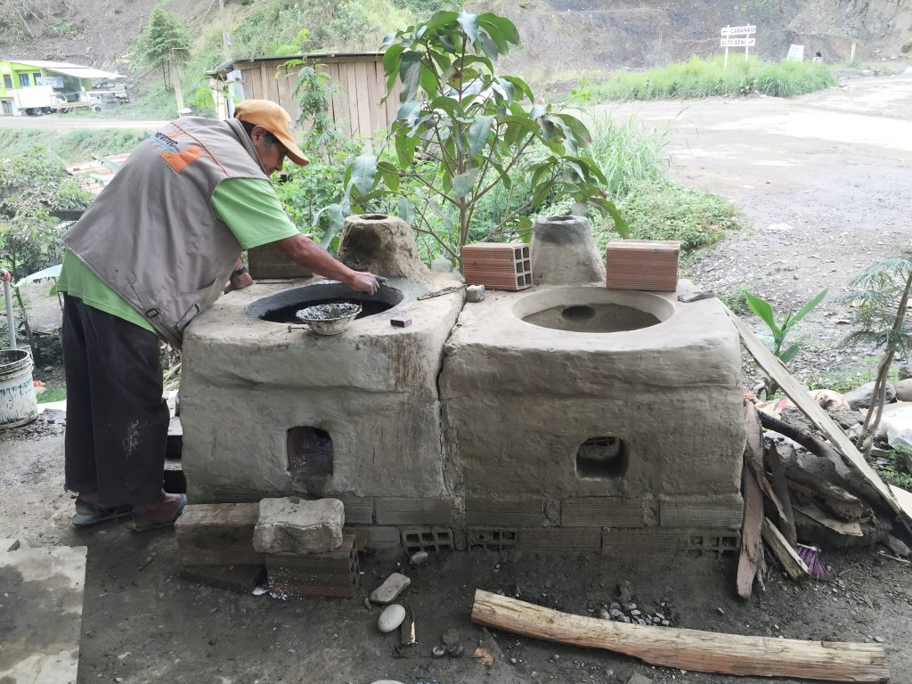 A Bolivian man is working on two large clay cookstoves.