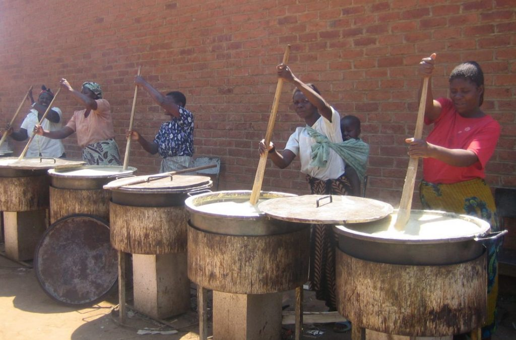 Volunteer mothers are cooking for school children in Malawi on large rocket stoves.