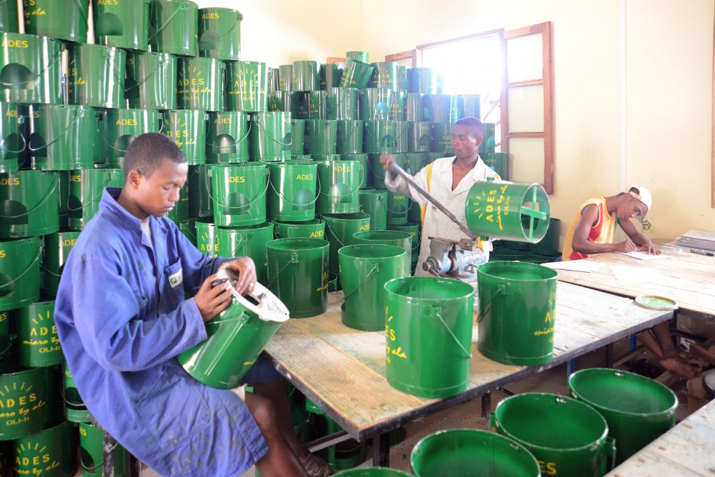 """Three Madagascan men are working on green metal cauldrons with a yellow line saying """"ADES"""" on them."""