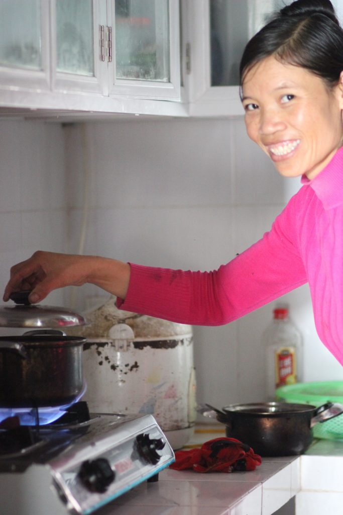 A Vietnamese woman is cooking on a biogas stove