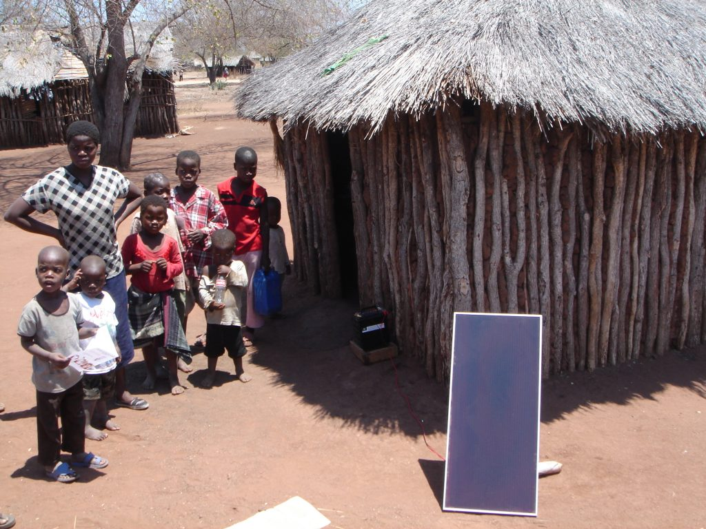 A Mozambiquan woman and some children are standing next to a solar panel leaning against their wooden house.